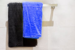 Black and blue towel on hanger in bathroom Stock Images