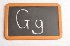 A black board with the alphabet letter G. In a capital and small letter Stock Photo