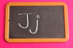 A black board with the alphabet letter J. In a capital and small letter Stock Images