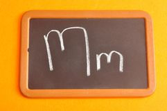A black board with the alphabet letter M. In a capital and small letter Stock Photo