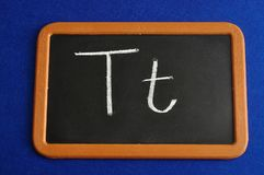 A black board with the alphabet letter T. In a capital and small letter Stock Images