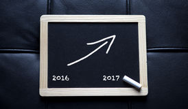 Black board with arrow upwards and new year 2017. Black board with the numbers 2016 and the new year 2017 with arrow pointing upwards Royalty Free Stock Images