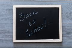 Black board with back to school inscription written on chalkboard and chalk on grey wooden background, starting new school year. Concept, elementary education royalty free stock photos