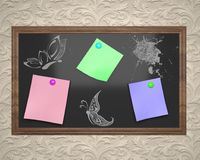 Black board in brown frame with colored stickers and white chalk Royalty Free Stock Photos