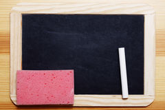 Black Board with chalk and sponge. Empty Black board with piece of chalk and a pink sponge Royalty Free Stock Photo