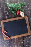 Black board for Christmas message over wooden background Royalty Free Stock Photos