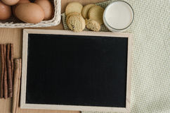 Black board,cookies and cinnamon on table Royalty Free Stock Photo