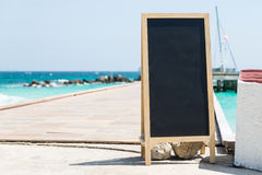Black board at port with clear blue sea, white sand and blue sky on island Stock Images