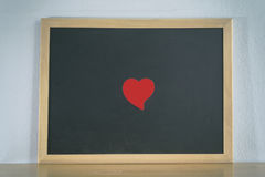 Black board and red-heart shape paper for note message on table Stock Images