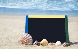 Black board on sandy beach Stock Photos