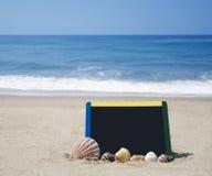 Black board on sandy beach. Black board with seashells on sandy beach on ocean background Royalty Free Stock Photos