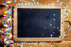 Black Board on Table with Streamers and Confetti Royalty Free Stock Image