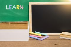 Black board and text book with school supplies. Learning concept. Black board and text book with school supplies in classroom. Learning concept royalty free stock photo