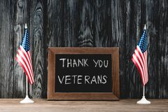 Board with thank you veterans lettering near flags of america