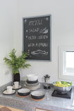 Black board on white wall in modern kitchen room with utensil Stock Photography