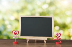 Black board on wood table top with sun and blur green tree bokeh background, Template mock up for display of product stock photography