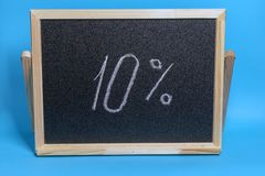Black Board in a wooden frame on a blue background with the inscription 10 percent. Mockup for black friday. Black Board in a wooden frame on a blue background royalty free stock photo