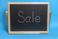 Black Board in a wooden frame on a blue background with the inscription sale. Mockup for shopping, sales, black friday. Black Board in a wooden frame on a blue royalty free stock photography