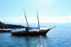 The black boat is sailing on the blue sea. stock image