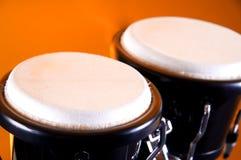 Black Bongos Isolated on Orange. A black set of bongos isolated against an orange background in the horizontal format Royalty Free Stock Image
