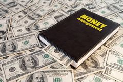 Black book with money and the inscription money management on banknotes background.  royalty free stock images