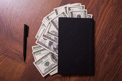 Black book, pen and money,business plan Royalty Free Stock Photos