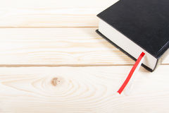 Black book with red and white bookmark on wooden table. Back to school. Copy space Stock Image