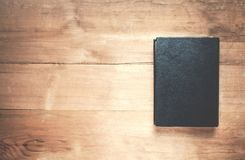 Black book on the wooden background. Stock Photo
