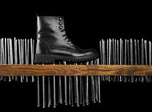 Black boot on a black background. man`s shoe on nails. Black boot on a black background The boot stands on large nails, pushing them into the board Stock Image