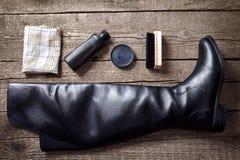Black boot, polish cream, brush and cloth Royalty Free Stock Photography