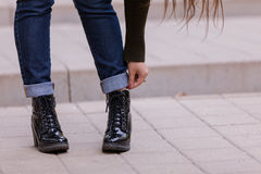 Black boots. The female feet in black varnish shoes Royalty Free Stock Photos