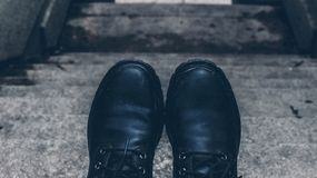 Black Boots with high contrast. Stairs. Black Boots with high contrast, up the ladder. City in winter. photo with cold and bluish tones. Industrial style Stock Photos