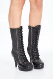 Black boots leather for women on white background driveways. Black leather boots with laces for Women on the feet of a woman stock images
