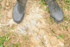 Black boots in muddy ground Royalty Free Stock Photography
