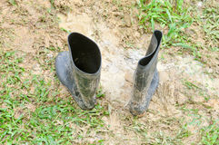 Black boots in muddy ground Royalty Free Stock Images