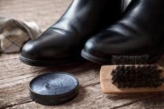 Black boots, polishing cream and brush Royalty Free Stock Images