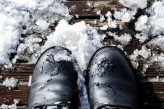 Black Boots in Snow with high contrast. Stepping on wooden boards. Black Boots with high contrast, in snow. City in winter. photo with warm tones. Sunny and Royalty Free Stock Photo