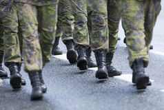 Black boots walking on a same pace. Stock Photos