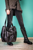 Black boots on woman legs and handbag Royalty Free Stock Photography