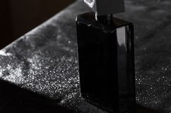 Totaly black bottle of masculine elegent fragrance on black leather background. Black bottle of expensive fragrance on black leather and water drops on it stock photo