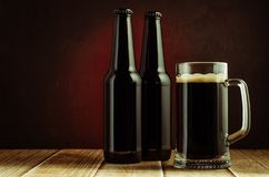 Black bottle and glass beer on a red background/black bottle and glass beer on a red background of a wooden shelf. Copyspace and. Selective focus three dark royalty free stock image