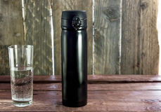 Black Bottle With Glass Of Water On A Wooden Desks Royalty Free Stock Photography