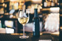 Black Bottle Beside Long-stem Wine Glass on Table stock photography