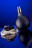 Black bottle of parfume and pearls Royalty Free Stock Image