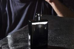 Black bottle of perfume on black surface, man in the back stock photography