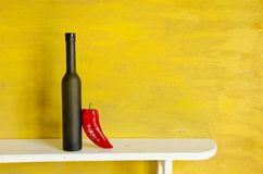 Black bottle and red pepper Royalty Free Stock Image