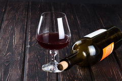 Black bottle of wine and wineglass Royalty Free Stock Photography