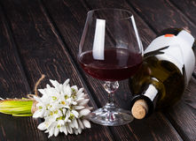 Black bottle of wine and wineglass on the wood background Stock Images