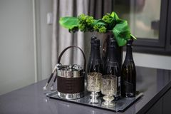 Black bottles of champagne stand on a table beside the dishes for ice and tongs in the background stock photography