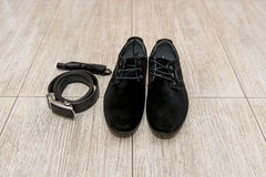 Black bow tie and leather shoes groom lying next to belt of trousers. Groom accessories, businessman, Stock Photos